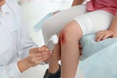Kvinnlig rengörande liten flickas för doktor skada för ben i klinik arkivbild