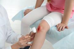 Kvinnlig rengörande liten flickas för doktor skada för ben i kliniken, closeup arkivfoto