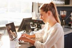 Kvinnlig restaurangchef som arbetar på räknaren Arkivfoton