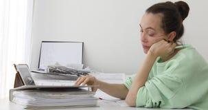 Kvinnlig revisor med mappar som arbetar på skrivbordet lager videofilmer