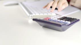 Kvinnlig revisor som i regeringsställning använder räknemaskinen på det vita skrivbordet lager videofilmer