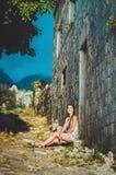 Kvinnlig romantisk kvinna som poserar i den gamla fästningen för Stari stång, Montenegro Brunbränd kvinnlig med långt hår, röda k Royaltyfria Foton