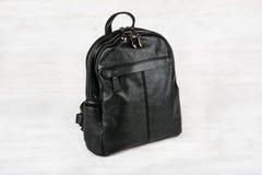 Kvinnlig ryggsäck för svart läder på vit träbakgrund Fotografering för Bildbyråer