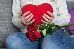 Kvinnlig rymmande stor röd hjärtakudde, i hand på hennes bröstkorg och att sitta på säng och rosor på knä arkivfoto