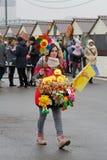 Kvinnlig säljare av ryssShrovetide små dockor i traditionella färgrika klänningar och med en skivtallrik på den ryska nationella  Arkivfoto