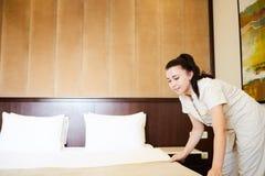 kvinnlig säng för danande för hushållningarbetarhembiträde med sängkläder på gästgivargårdrum Gjord danandesäng i rum royaltyfri bild