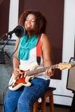 Kvinnlig sångare With Eyes Closed som spelar gitarren in Arkivbilder