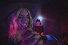 Kvinnlig sångare med coworkeren som spelar pianot i upplyst nattklubb Royaltyfri Fotografi