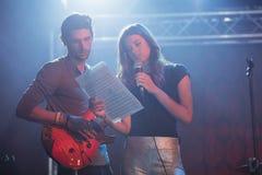Kvinnlig sångare med den manliga gitarristen som öva på nightblub arkivfoto