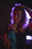 Kvinnlig sångare med handen i hår som utför i nattklubb Fotografering för Bildbyråer
