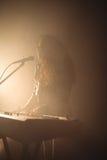 Kvinnlig sångare med pianot i upplyst nattklubb Arkivbild