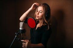 Kvinnlig sångare som antecknar en sång i musikstudio Arkivfoton