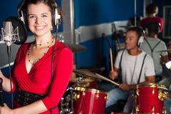 Kvinnlig sångare som antecknar ett spår i studio Arkivbild