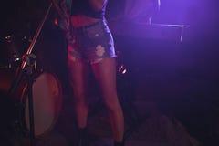 Kvinnlig sångare som utför medan man som spelar pianot i upplyst nattklubb Royaltyfri Fotografi