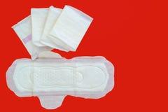 Kvinnlig sanitär servett, ett absorberande objekt som är slitet vid en kvinna, medan menstruera, på röd bakgrund Arkivfoto
