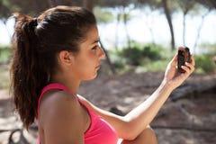 Kvinnlig seende översikt för brunett på en GPS apparat Arkivfoton