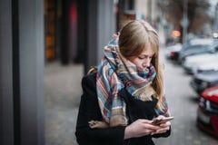 Kvinnlig seende mobil enhet på laget för halsduk för ull för ung caucasian kvinna för höstgata det bärande royaltyfri fotografi