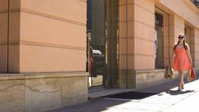 Kvinnlig shopaholic gå gata med påsar, consumerism, gåvaköp, försäljning royaltyfri bild
