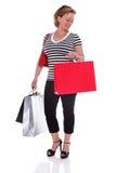 Kvinnlig shoppare med shoppingpåsar som kontrollerar hennes isolerade klocka. Royaltyfri Foto