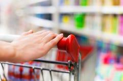Kvinnlig shoppare med spårvagnen på supermarket Arkivbild