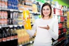 Kvinnlig shoppare som söker för drycker Arkivbilder