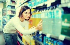 Kvinnlig shoppare som söker för drycker Arkivfoton