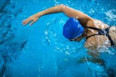 Kvinnlig simmare i en inomhus simbassäng - göra krypande Fotografering för Bildbyråer