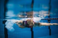 Kvinnlig simmare i inre simbassäng för handling royaltyfri foto