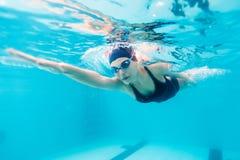 Kvinnlig simmare som forsar till och med vatten i pöl royaltyfri bild