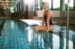 Kvinnlig simmare som vilar på kanten av en pöl arkivbild