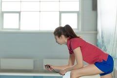 Kvinnlig simninglagledare som ser stoppuren nära poolside Royaltyfri Bild