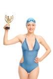 Kvinnlig simningmästare som rymmer en guld- kopp arkivfoton