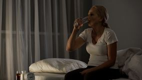 Kvinnlig sjukhuspatient som dricker piller med vattennatten, sittande säng, sömnlöshet royaltyfri bild