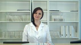 Kvinnlig sjukhusreceptionist som ser kameran lager videofilmer