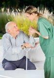 Kvinnlig sjuksköterska Helping Senior Man som ska fås upp från Fotografering för Bildbyråer