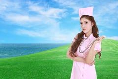 Kvinnlig sjuksköterska med stetoskopet med fältet för grönt gräs Arkivbild