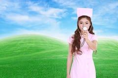 Kvinnlig sjuksköterska med stetoskopet med fältet för grönt gräs Arkivbilder