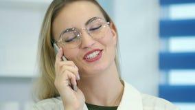 Kvinnlig sjuksköterska på sjukhusmottagandet som talar på telefonen stock video
