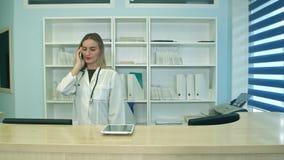 Kvinnlig sjuksköterska på tidsbeställningar för påringningar och för planlagd för sjukhusmottagande svarande tålmodiga arkivfilmer