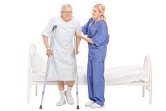 Kvinnlig sjuksköterska som hjälper en hög patient med kryckor Arkivbild