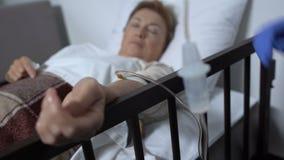 Kvinnlig sjuksköterska som sätter droppande till den sjuka kvinnan, kemoterapikurs, sjukhusvård stock video