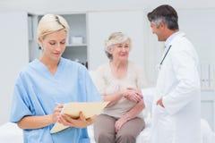 Kvinnlig sjuksköterskadanande anmäler medan doktorn och patienten som skakar händer Arkivbild