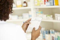 Kvinnlig sjuksköterska för UK i apotek med receptet Royaltyfri Foto