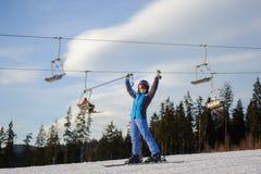 Kvinnlig skidåkare mot skidlift och skog på en solig dag Royaltyfri Bild
