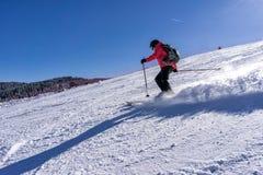 Kvinnlig skidåkare på en lutning Fotografering för Bildbyråer