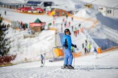 Kvinnlig skidåkare på en skidalutning på en solig dag Royaltyfri Foto