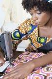 Kvinnlig skräddare för afrikansk amerikan som syr den mönstrade torkduken på symaskinen Arkivfoton
