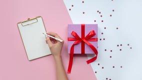Kvinnlig skrivande önskelista nära julgåvan kopiera avstånd royaltyfria foton