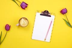 Kvinnlig skrivbords- sammansättning med skrivplattan för tomt ark, blyertspenna, kaffekopp, tulpanbukett på gul bakgrund Girlie a arkivfoto