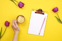 Kvinnlig skrivbords- sammansättning med skrivplattan för tomt ark, blyertspenna, kaffekopp, tulpanbukett på gul bakgrund Girlie a arkivbild